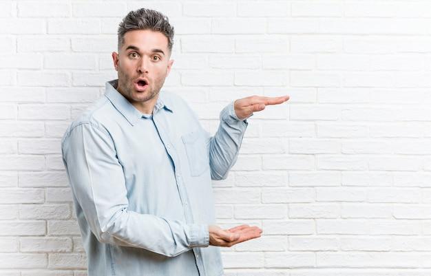 Giovane uomo bello contro un muro di mattoni scioccato e stupito tenendo un copyspace tra le mani. Foto Premium