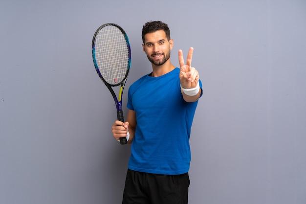 Giovane uomo bello del tennis che sorride e che mostra il segno di vittoria Foto Premium