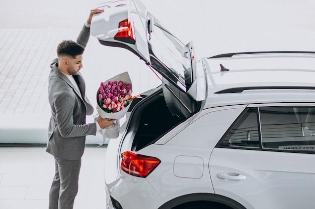 Giovane uomo bello di affari che consegna mazzo di bei fiori Foto Gratuite