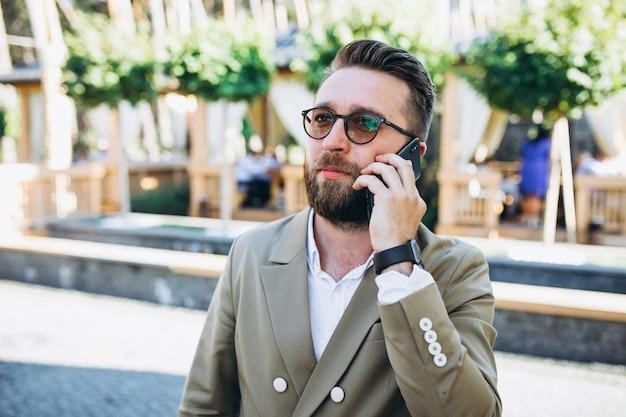 Giovane uomo bello di affari che per mezzo del telefono Foto Gratuite