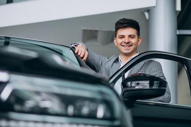 Giovane uomo bello di affari che sceglie un'automobile in una sala d'esposizione dell'automobile Foto Gratuite