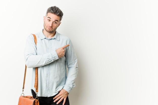 Giovane uomo bello di affari che sorride e che indica da parte, mostrando qualcosa nello spazio. Foto Premium