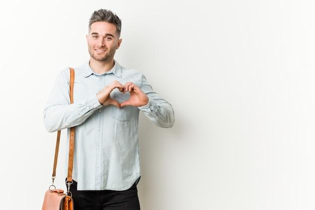 Giovane uomo bello di affari che sorride e che mostra una forma del cuore con le mani. Foto Premium