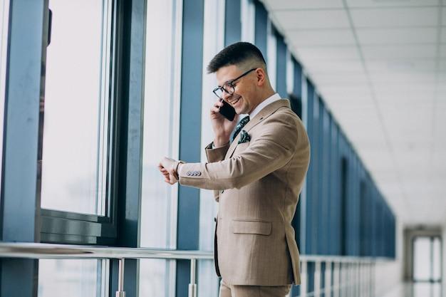 Giovane uomo bello di affari che sta con il telefono all'ufficio Foto Gratuite