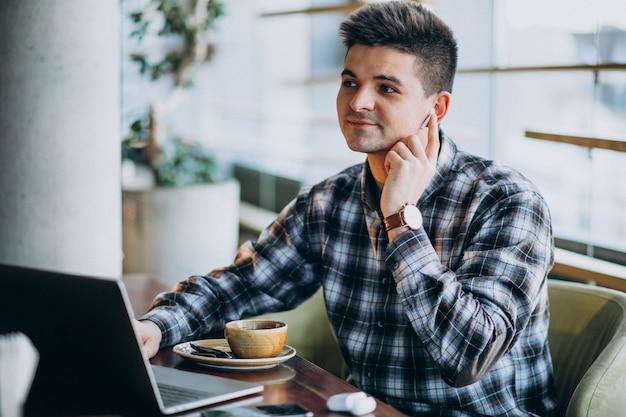 Giovane uomo bello di affari che utilizza computer portatile in un caffè Foto Gratuite