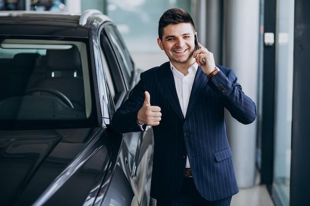Giovane uomo bello di affari in una sala d'esposizione dell'automobile che sceglie un'automobile Foto Gratuite