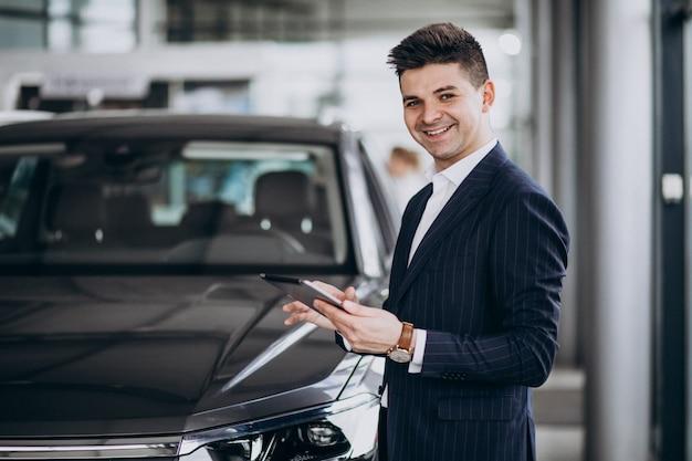 Giovane uomo bello di affari in uno showrrom dell'automobile Foto Gratuite