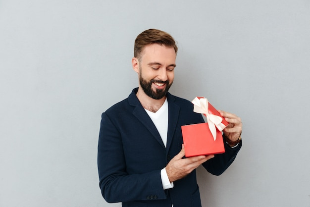 Giovane uomo bello felice che esamina regalo rosso isolato Foto Gratuite