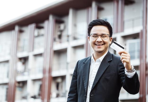 Giovane uomo bello godere shopping online sul cellulare con carta di credito. Foto Gratuite