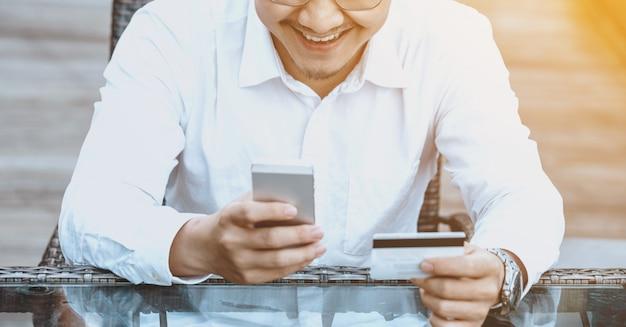 Giovane uomo bello godere shopping online sul telefono cellulare con carta di credito. Foto Gratuite