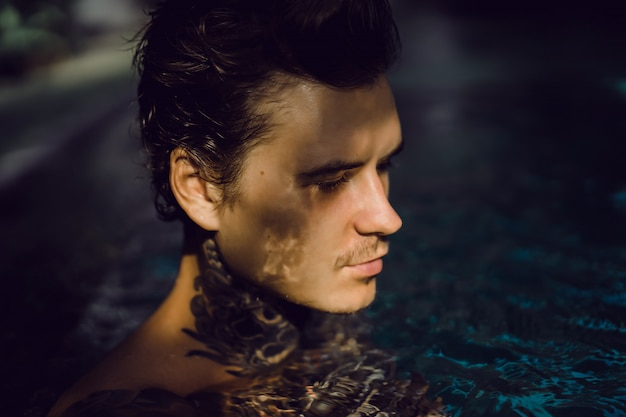 Giovane uomo bello in tatuaggi che riposa nella piscina all'aperto. Foto Gratuite