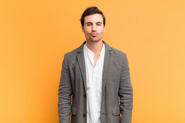 Giovane uomo bello premendo le labbra insieme a un'espressione carina, divertente, felice, adorabile, inviando un bacio Foto Premium
