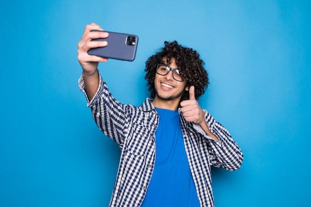 Giovane uomo bello riccio che fa un selfie sopra la parete blu isolata Foto Gratuite