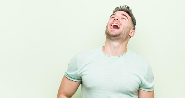 Giovane uomo bello rilassato e felice ridendo, collo allungato mostrando i denti. Foto Premium