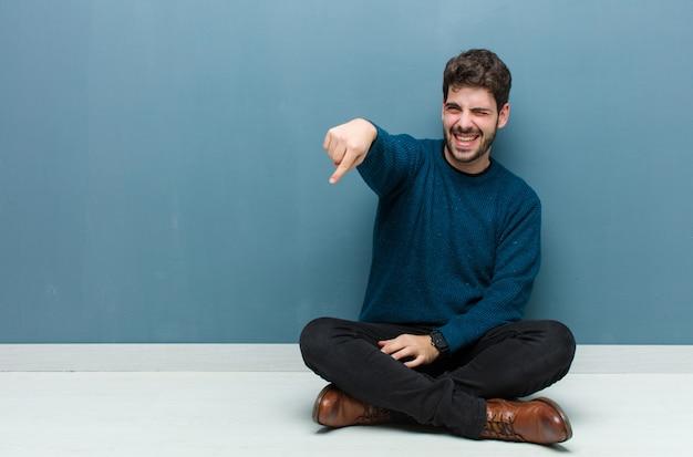 Giovane uomo bello seduto sul pavimento ridendo di te, indicando la fotocamera e prendendo in giro o deridendoti Foto Premium