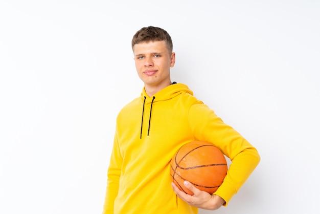 Giovane uomo bello sopra bianco isolato con la palla di pallacanestro Foto Premium