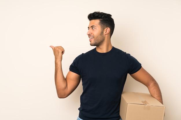 Giovane uomo bello sopra la parete isolata che tiene una scatola per spostarla in un altro sito e indicare il lato Foto Premium