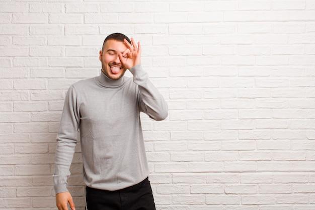 Giovane uomo bello sorridente felicemente con una faccia buffa, scherzando e guardando attraverso lo spioncino, spiando i segreti contro il muro piatto Foto Premium