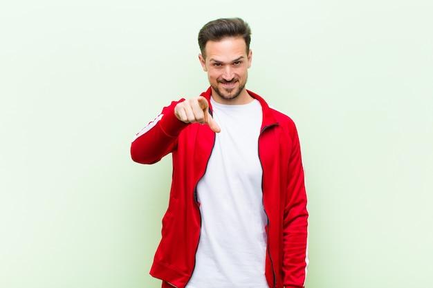 Giovane uomo bello sportivo o monitor che punta alla fotocamera con un sorriso soddisfatto, fiducioso, amichevole, scegliendovi contro la parete piatta Foto Premium