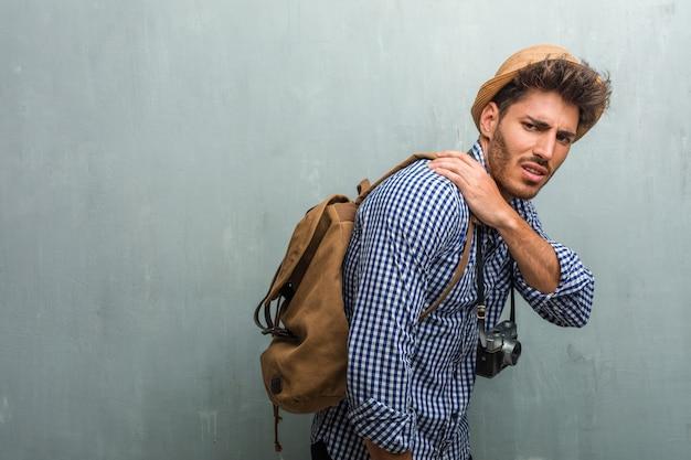 Giovane uomo bello viaggiatore che indossa un cappello di paglia, uno zaino e una macchina fotografica con dolore alla schiena a causa di stress da lavoro, stanco e astuto Foto Premium