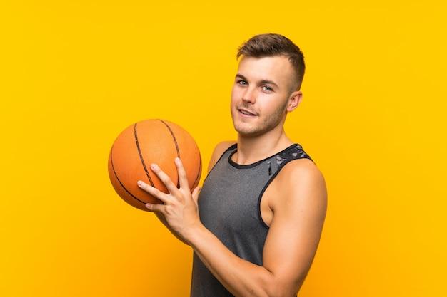 Giovane uomo biondo bello che tiene una palla del canestro sopra la parete gialla isolata Foto Premium