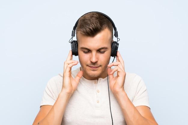 Giovane uomo biondo bello sopra la parete blu che ascolta la musica con le cuffie Foto Premium