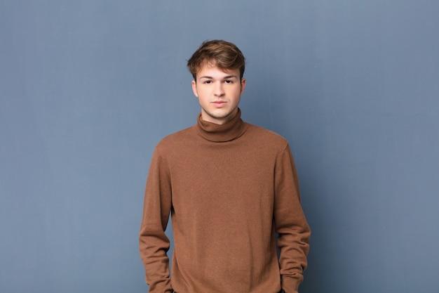 Giovane uomo biondo che copre il viso con le mani, sbirciando tra le dita con espressione sorpresa e guardando al lato sopra il muro Foto Premium