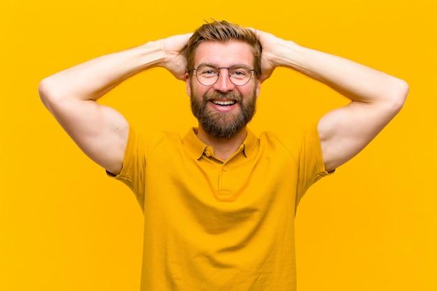 Giovane uomo biondo che sembra felice, spensierato, amichevole e rilassato godendo la vita e il successo, con un atteggiamento positivo muro arancione Foto Premium