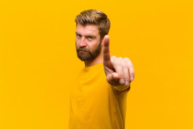 Giovane uomo biondo che sorride con orgoglio e con fiducia facendo trionfante la posa numero uno, sentendosi come un leader contro la parete arancione Foto Premium