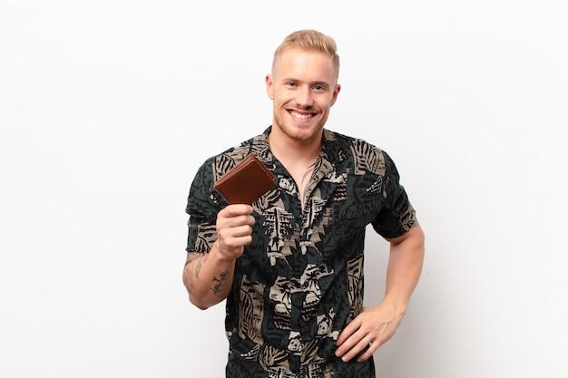 Giovane uomo biondo che sorride felicemente con una mano sull'anca e un atteggiamento fiducioso, positivo, orgoglioso e amichevole con un portafoglio Foto Premium