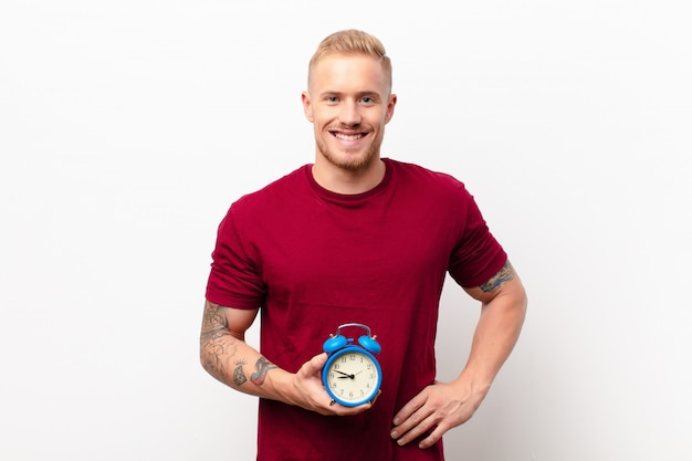 Giovane uomo biondo che sorride felicemente con una mano sull'anca e un atteggiamento sicuro, positivo, orgoglioso e amichevole contro il muro bianco che tiene una sveglia Foto Premium