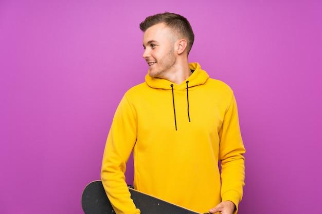 Giovane uomo biondo che tiene un pattino che sembra laterale Foto Premium