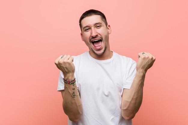 Giovane uomo casuale che incoraggia spensierato ed eccitato. concetto di vittoria Foto Premium