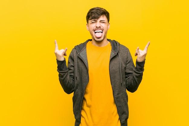 Giovane uomo casuale ispanico che mostra gesto della roccia con le dita Foto Premium