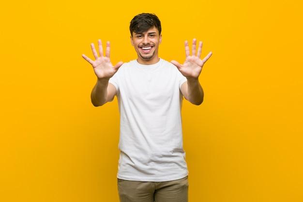 Giovane uomo casuale ispanico che mostra numero dieci con le mani. Foto Premium