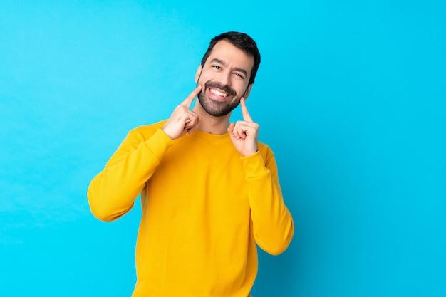 Giovane uomo caucasico sopra la parete blu isolata che sorride con un'espressione felice e piacevole Foto Premium