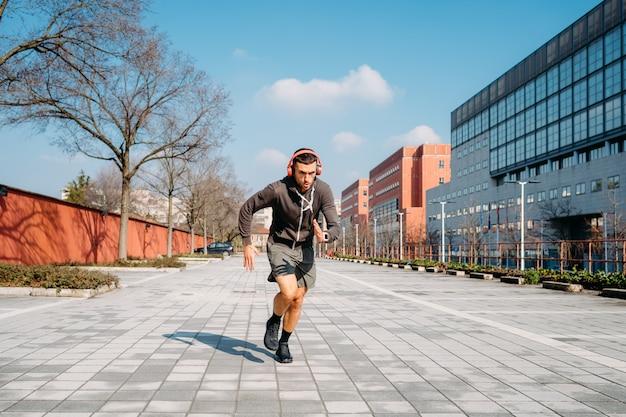 Giovane uomo che corre allenamento all'aperto Foto Premium