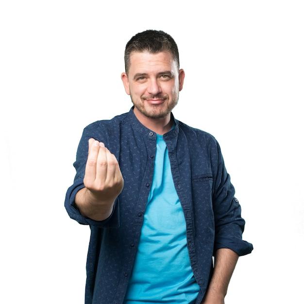 Giovane uomo che indossa un vestito blu. facendo il gesto di denaro. Foto Gratuite
