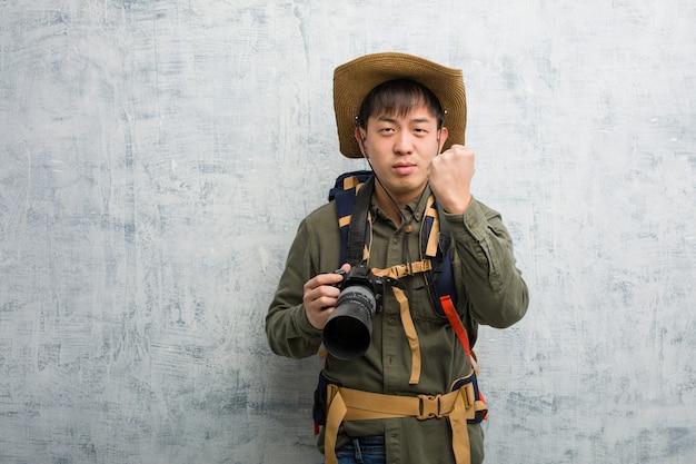 Giovane uomo cinese dell'esploratore che tiene una macchina fotografica che mostra pugno alla parte anteriore Foto Premium