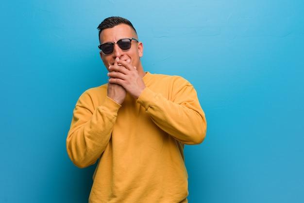 Giovane uomo colombiano ridendo di qualcosa, che copre la bocca con le mani Foto Premium