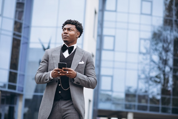 Giovane uomo d'affari africano che per mezzo del telefono Foto Gratuite