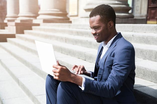 Giovane uomo d'affari africano che si siede sui punti facendo uso del computer portatile a all'aperto Foto Gratuite