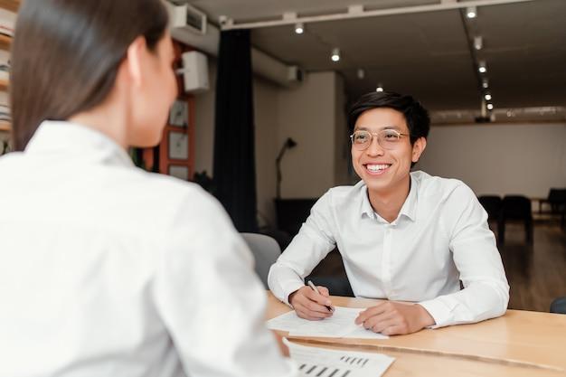 Giovane uomo d'affari asiatico sul colloquio di lavoro con una donna in ufficio Foto Premium