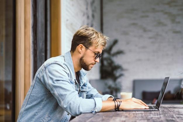 Giovane uomo d'affari attraente in un caffè lavora per un laptop, beve caffè. Foto Gratuite