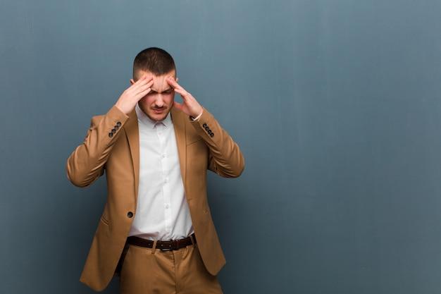 Giovane uomo d'affari bello che sembra stressato e frustrato, lavorando sotto pressione con un mal di testa e travagliato da problemi contro la parete piatta Foto Premium