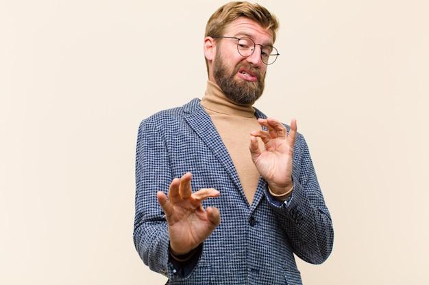 Giovane uomo d'affari biondo sentendosi disgustato e nauseato, indietreggiando da qualcosa di brutto, puzzolente, dicendo schifo Foto Premium
