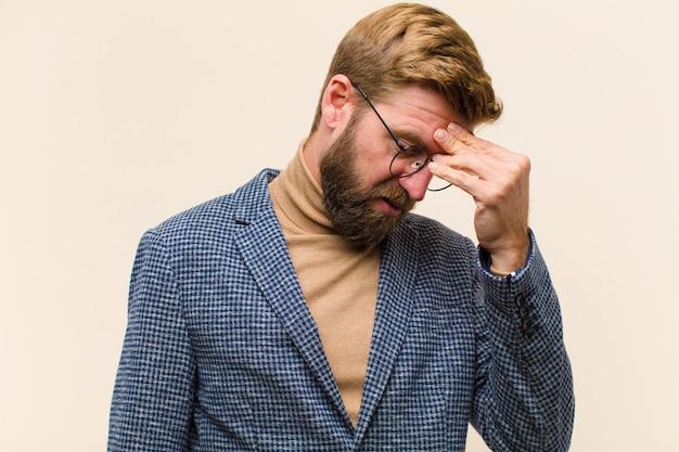 Giovane uomo d'affari biondo sentirsi stressato infelice e frustrato fronte commovente e sofferenza di emicrania di forte mal di testa Foto Premium