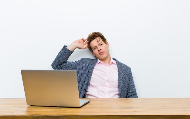 Giovane uomo d'affari capo rosso che lavora nel suo scrittorio con un computer portatile Foto Premium