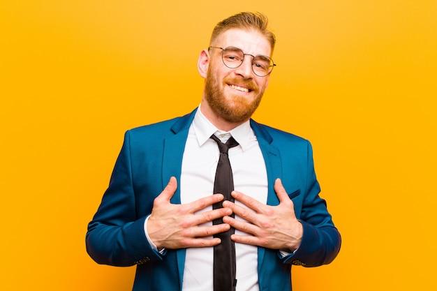 Giovane uomo d'affari capo rosso che sembra felice, sorpreso, fiero ed eccitato, indicando se stesso sull'arancia Foto Premium