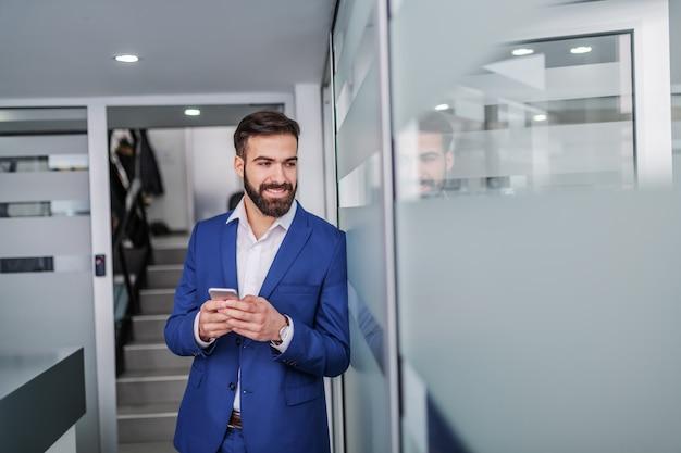 Giovane uomo d'affari caucasico bello in vestito che sta nel corridoio della ditta di broker e che per mezzo dello smart phone. Foto Premium
